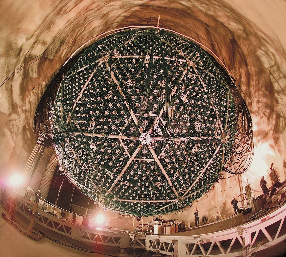 A photo from the Sudbury Neutrino Observatory. This 18 meter sphere is a Cherenkov telescope containing 9,500 Photomultiplier Tubes and is immersed into a tank of 1,000 tons of Heavy Water (D2O). More than 50 trillion solar neutrinos pass through our bodies every second, but they are so weakly interacting that we need detectors of this scale to detect them.  Image courtesy LBL, Roy Kaltschmidt