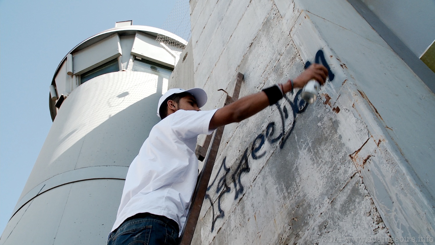Painting graffiti on the Israeli separation barrier at Bethlehem