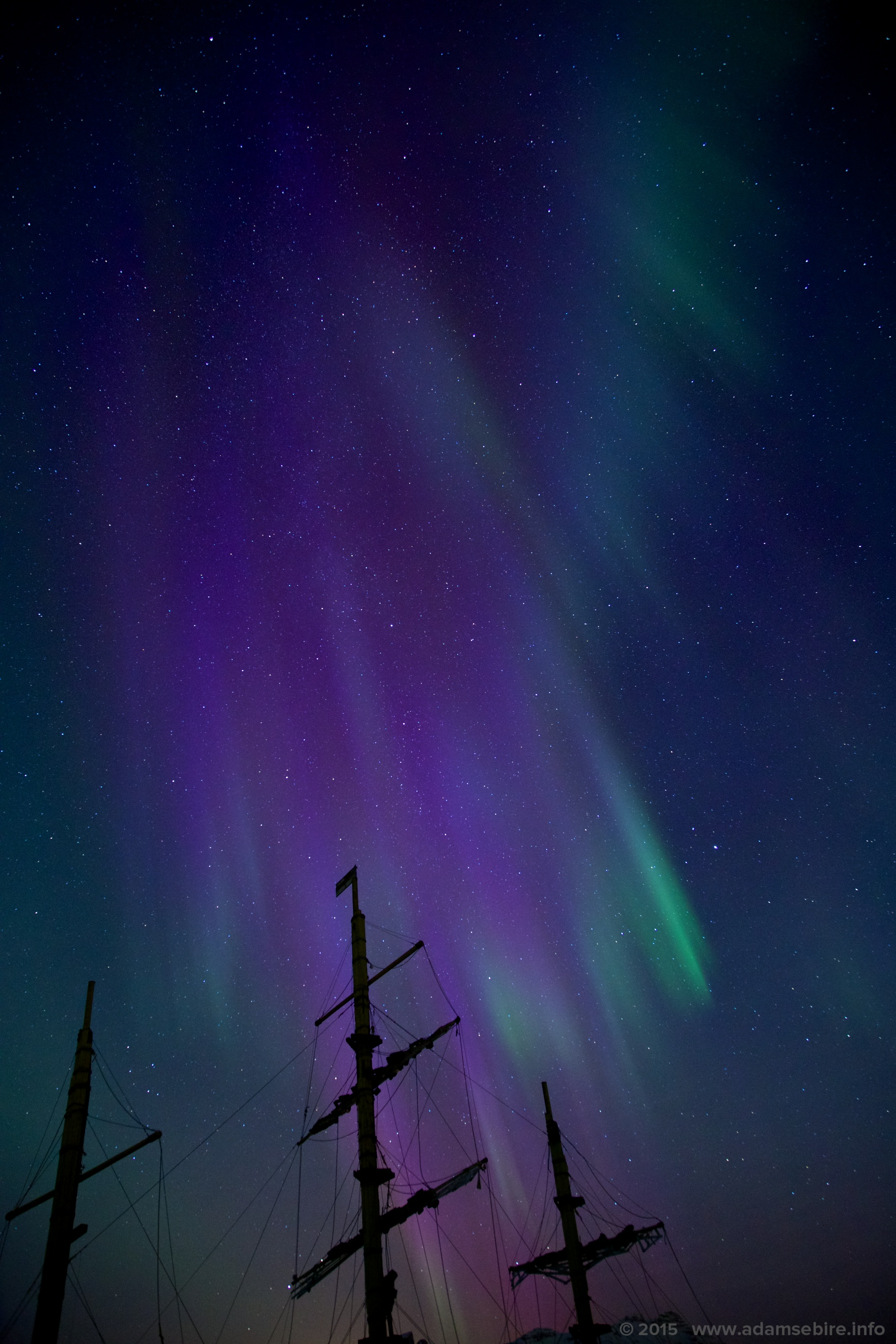 Violet aurora borealis due to ionised nitrogen over ship's masts in Arctic Norway