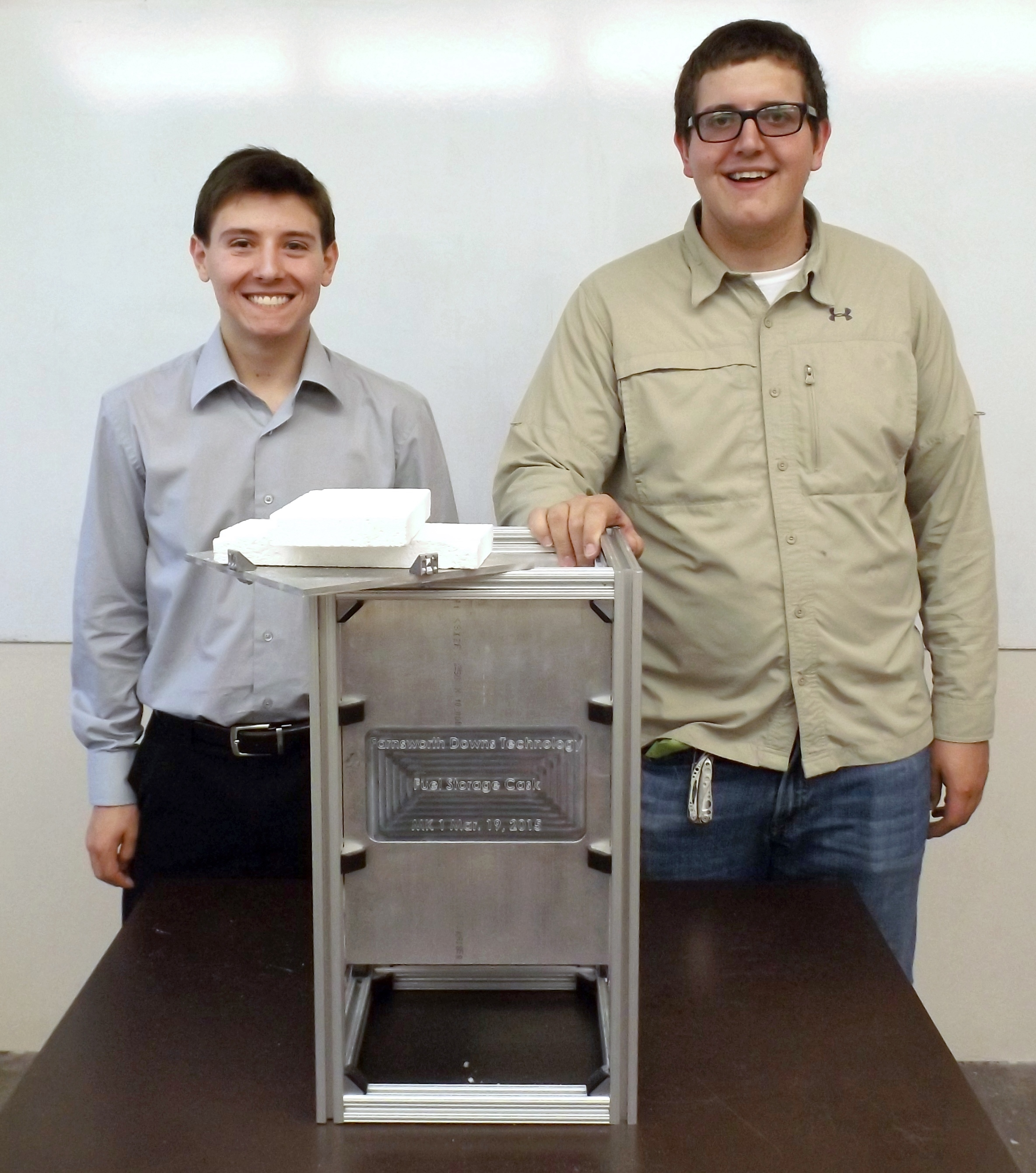 Adrian Del Grosso (left) and Conrad Farnsworth (right) stand with their first fuel cask prototype in their lab space on the SDSM&T campus in Rapid City, SD.