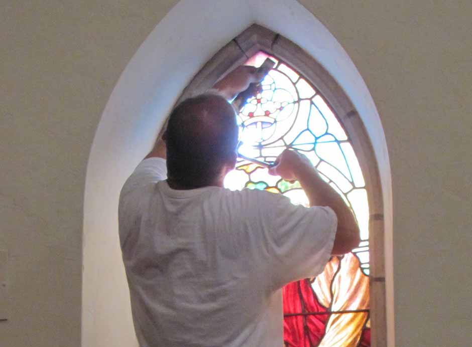 Curry Wells removes putty around the damaged window.