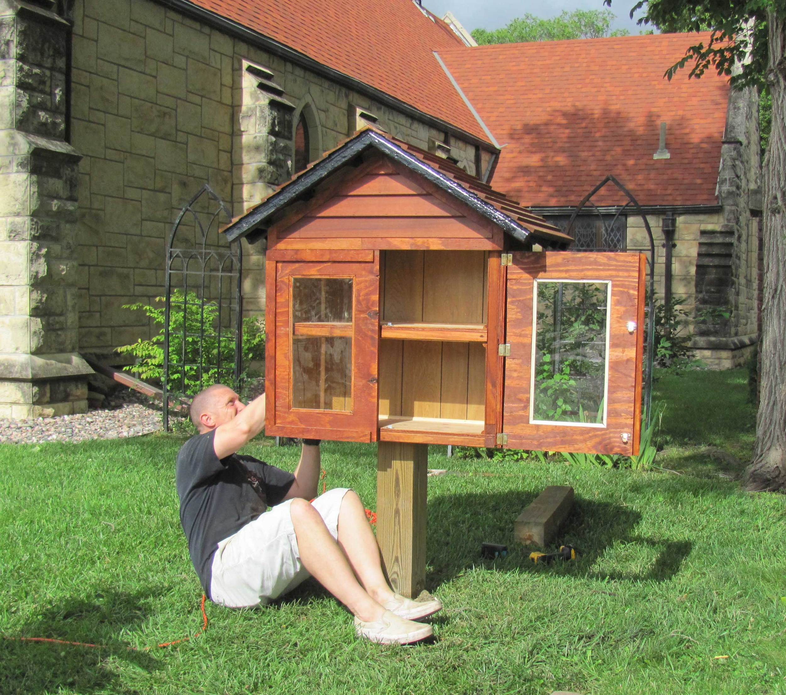 Justin Shaw installing St. John's Little Free Library. Justin built the library over the winter.