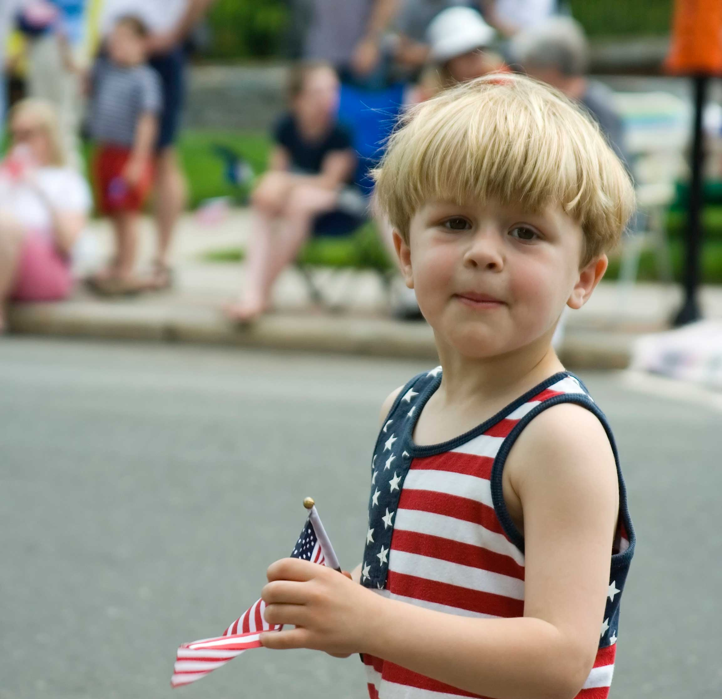 A patriotic parade watcher is temporarily distracted from harvesting parade candy.