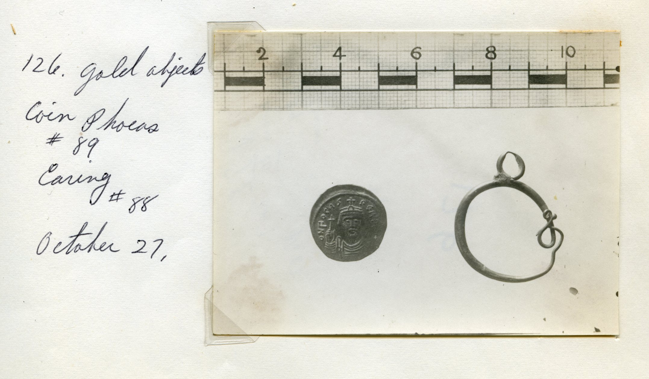 Coin of Emperor Phocas (602-610) found in House III on the tell. Photographed in 1921, alongside a gold earring now found in the University of Pennsylvania collection. The coin is kept at the Rockefeller Museum, Jerusalem.
