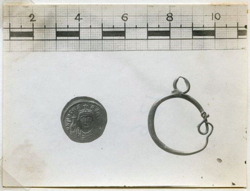 Photograph of the earring and a coin found in the debris of House III.