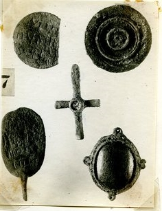 Photograph depicting a number of jewelry items from the 1922 excavation season of the Northern Cemetery tombs. The Rider Saint Amulet is depicted upside down in the lower left corner.