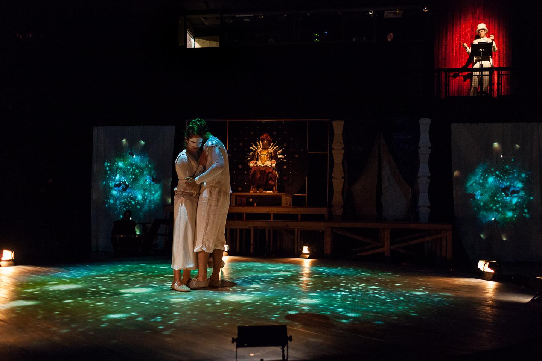 Elizabeth (Regan Linton) watches as God (Matt MacNelly) conducts the Earth (Christian Huerta-Murillo) and Moon (Lindsay Shield).