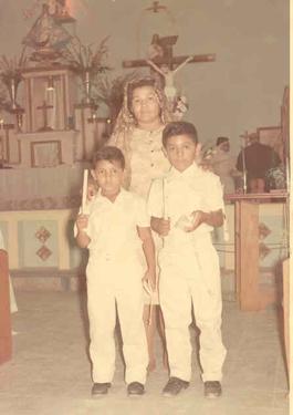 A la izquierda Juan Carlos y a la derecha su hermano Raymundo Manuel, atrás su Madrina. Cuando Juan Carlos tenía 8 años de edad hizo su primera comunión al lado de su hermano mayor Raymundo Manuel.