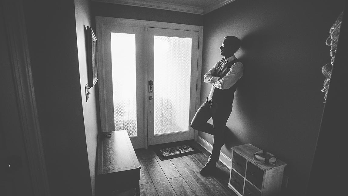 the groom standing in a hallway.jpg
