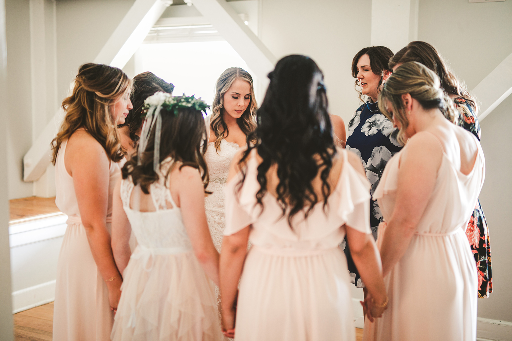 The bridesmaids praying with the bride before the wedding ceremony