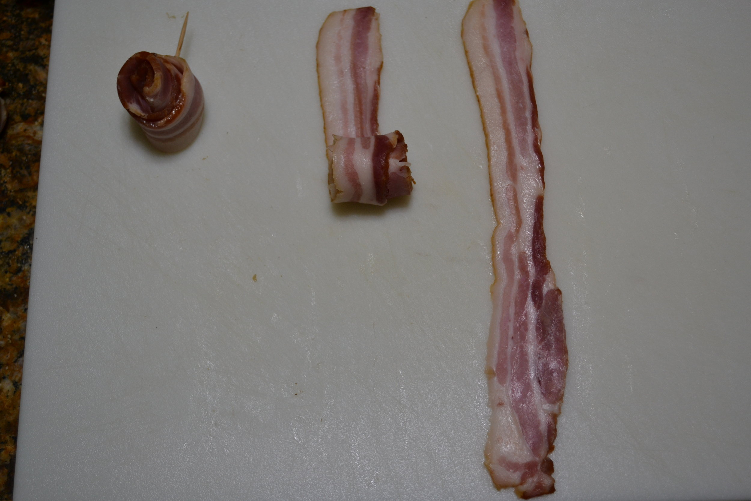 Be sure to roll but not in a real tight roll.  You may need to do this a few times to get what you feel looks like a rose.      After you have mastered this and have a bacon rose the way you want it, you need to place a toothpick thru the slice to hold it in place.  Next, place in an aluminum muffin pan that you punched  3 - 4 holes in the bottom.  These holes will allow the bacon grease to drain out as it cooks.