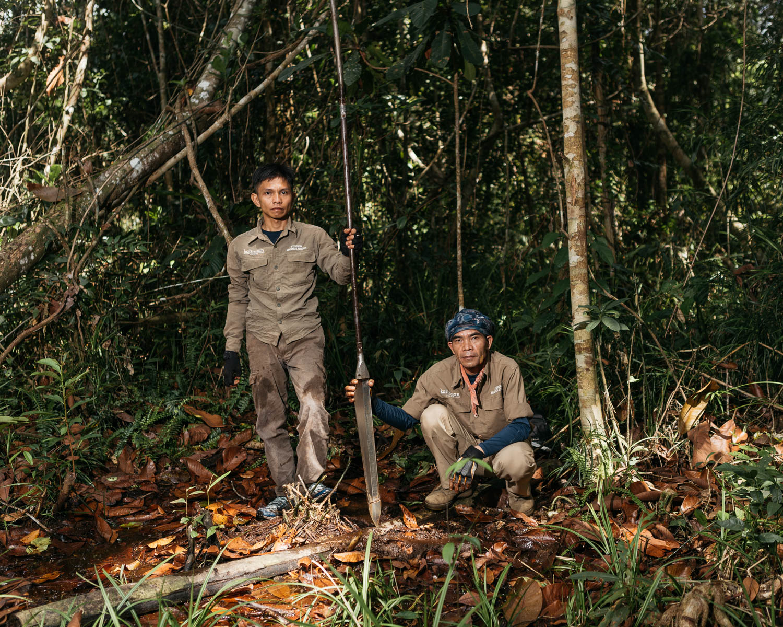 Portrait of Radius (left) and Hendri Saleh (right), staffs of PT Rimba Makmur Utama, after measuring the depth of peat in the forest.