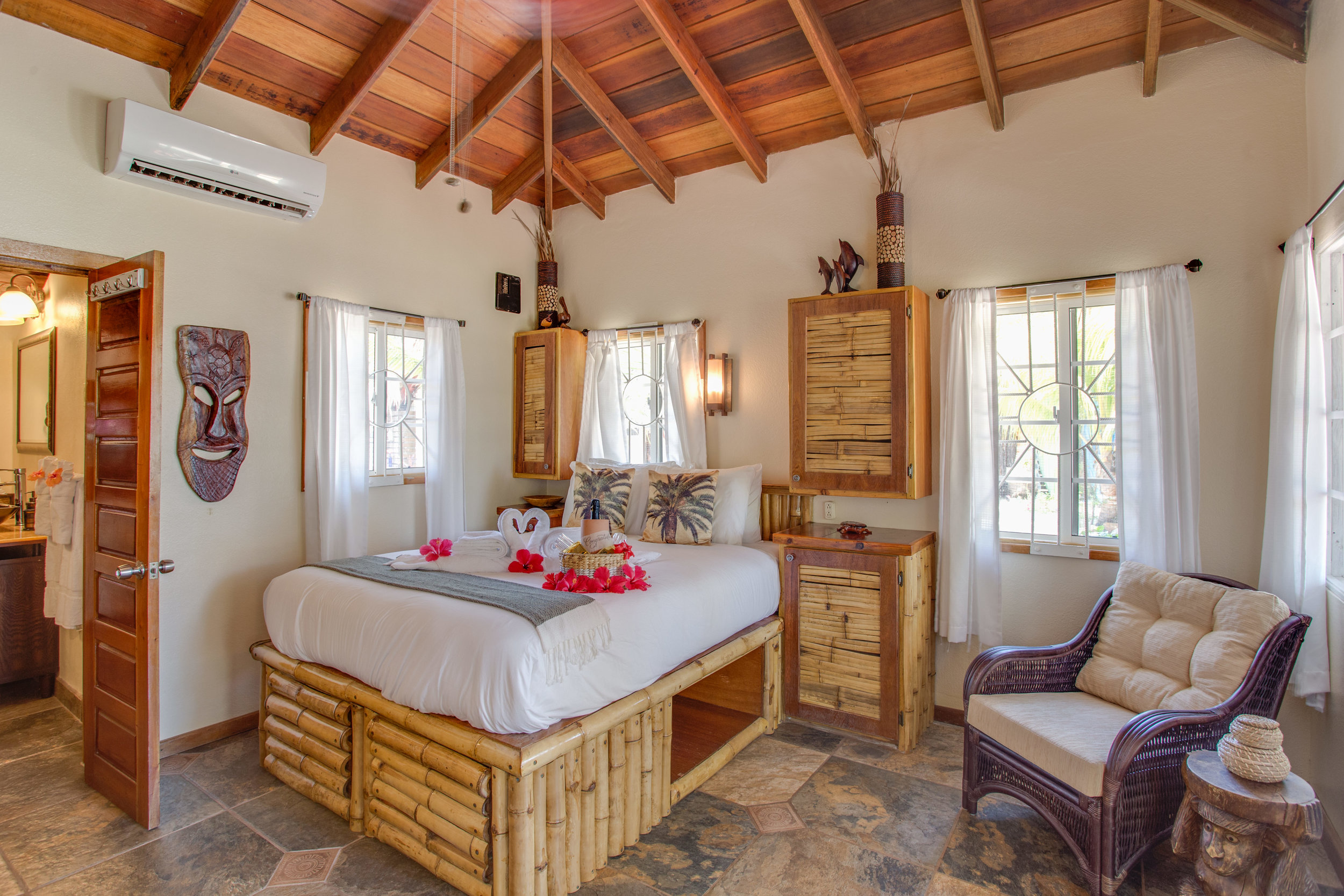 These traditional Belizean cabanas have luxury bedding, Belizean wood ceiling, bamboo accents, with exotic furniture and local art