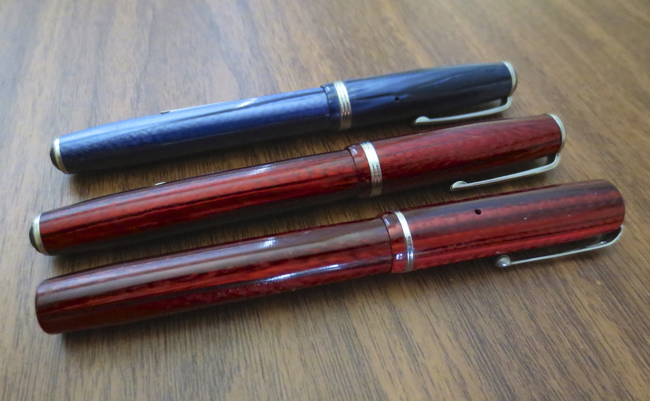 "Three Esterbrooks, from top:  Blue ""J"", Red ""J"", and Dollar Pen.  I bought all of these pens as parts of lots on eBay, and restored them myself.  Lever filler pens, which fill using a pressure bar and an ink sac, are inexpensive repairs and can be done at home once you make a small investment in supplies.  If you are interested in starting a larger collection, it's worth learning this skill."