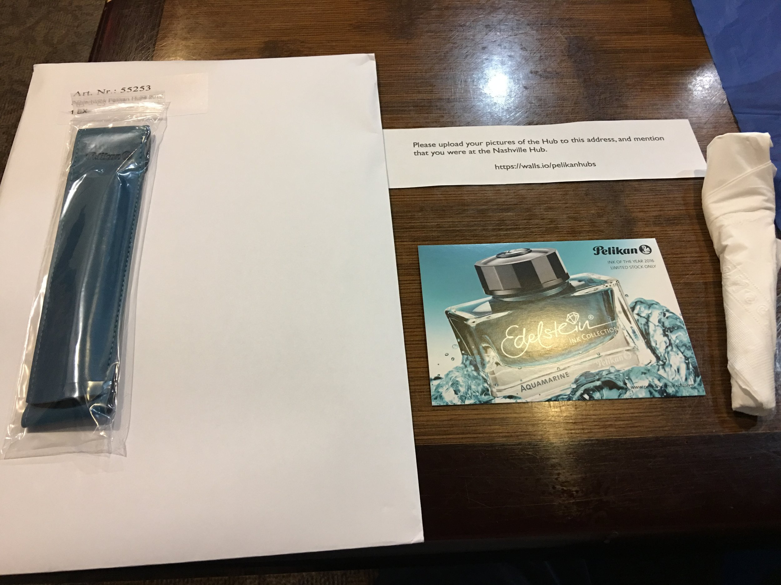 Pelikan Hubs Swag, from left: a quiver-style pen holder that attaches to a notebook, a pad of paper, and an Edelstein ink postcard,  Everyone who registered also received a bottle of Edelstein Aquamarine Ink.