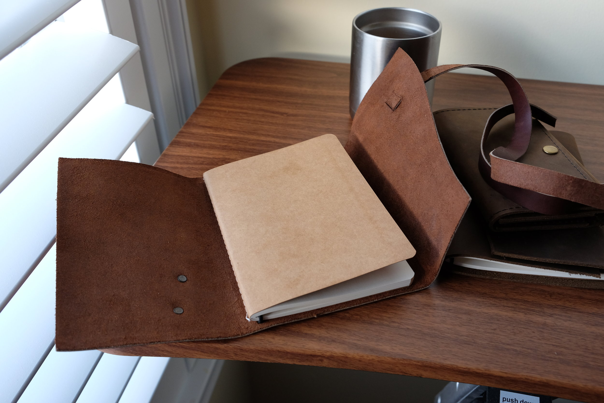 The medium-sized Triple Wrap journal open. The refill on the medium journal is held in by an elastic cord, similar to the Midori Traveler's Notebook.