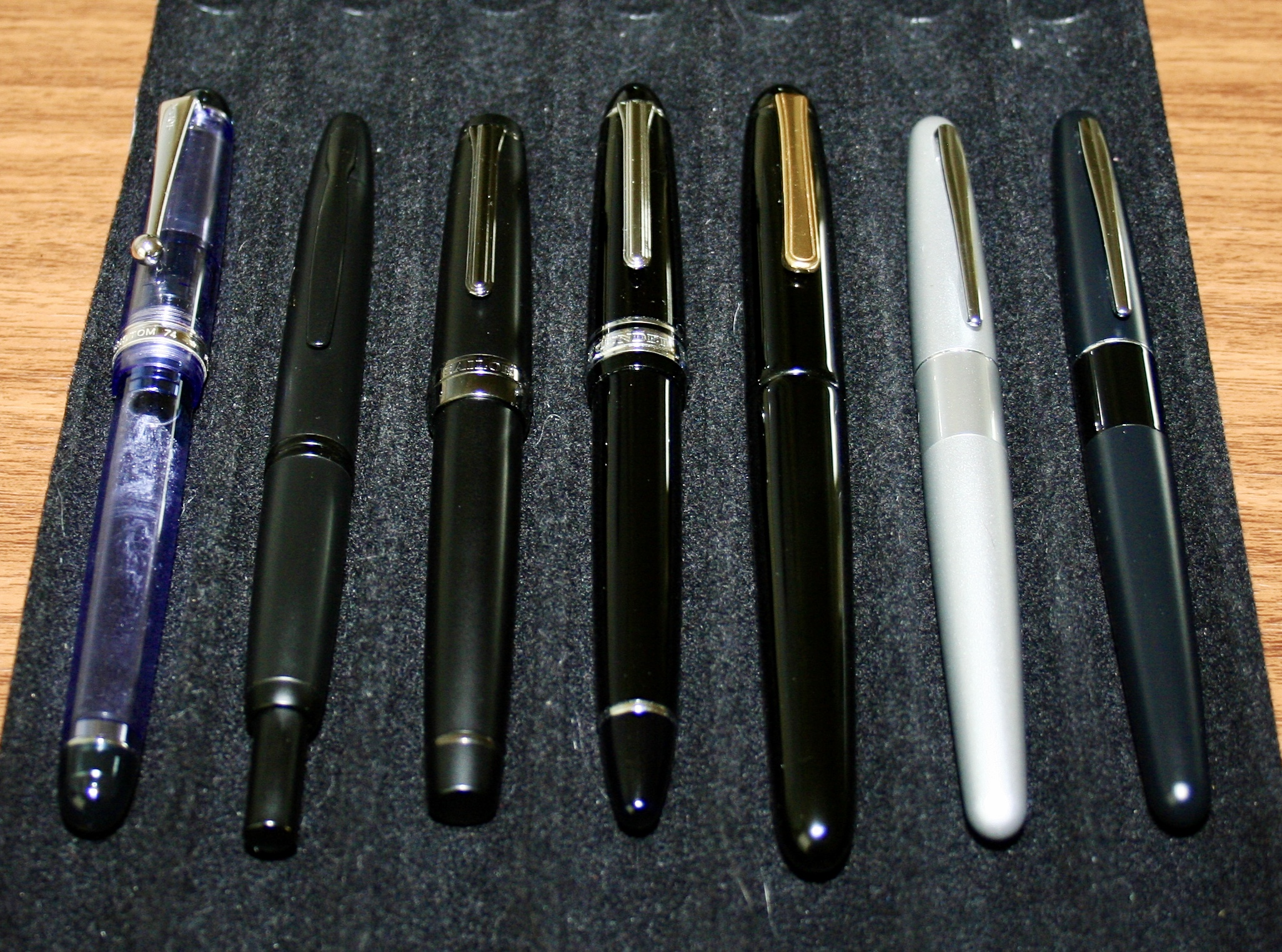 An older photo of the Custom 74 violet demonstrator (far left) that I no longer have. This picture offers a good size comparison of the Custom 74 to the (from left)  Pilot Vanishing Point ,  Sailor Pro Gear Imperial Black ,  Sailor 1911 Large ,  Nakaya Portable Writer , and the  Pilot Metropolitan .