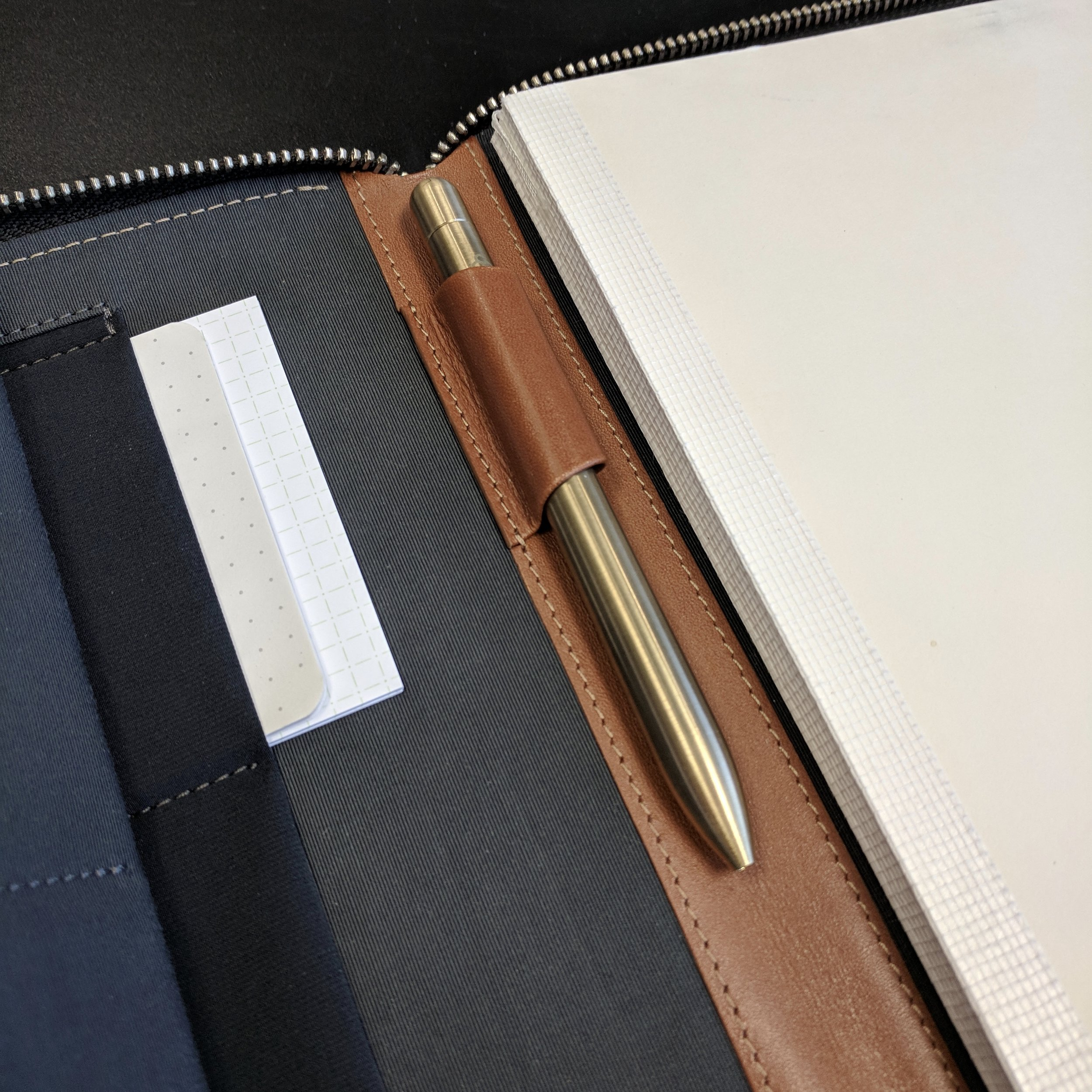 """Due to the lack of a clip on the  Baron Fig Squire (Brass """"Key"""" version shown here) , this may not be the most """"practical"""" pairing I can think of but I like the combination of the patina on the brass and the leather portfolio.The pen loop is pretty slim, so don't expect that it will hold your fat fountain pens."""