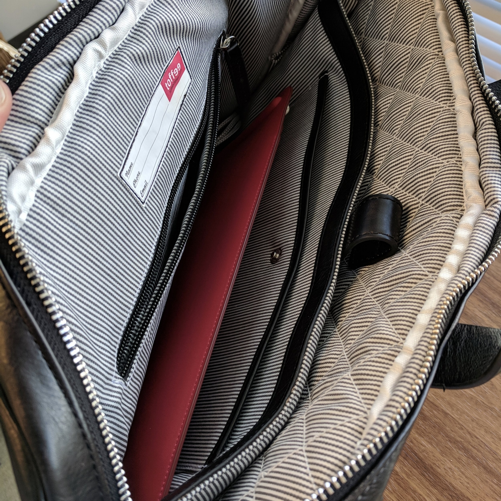 """The interior of the Toffee Lincoln, from left to right: a deep zippered pocket; the main compartment holding my 10.5 inch iPad in leather case, for scale; a smaller """"tablet pocket,"""" which is large enough to hold the 10.5 inch iPad in its keyboard cover; and a 15-inch laptop slot, with quilted padding. There is a leather strap to secure both the laptop and tablet."""