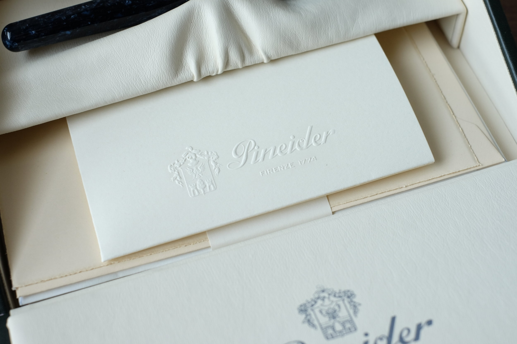 Pineider pens ship in a leatherette box containing a small assortment of Pineider stationery.
