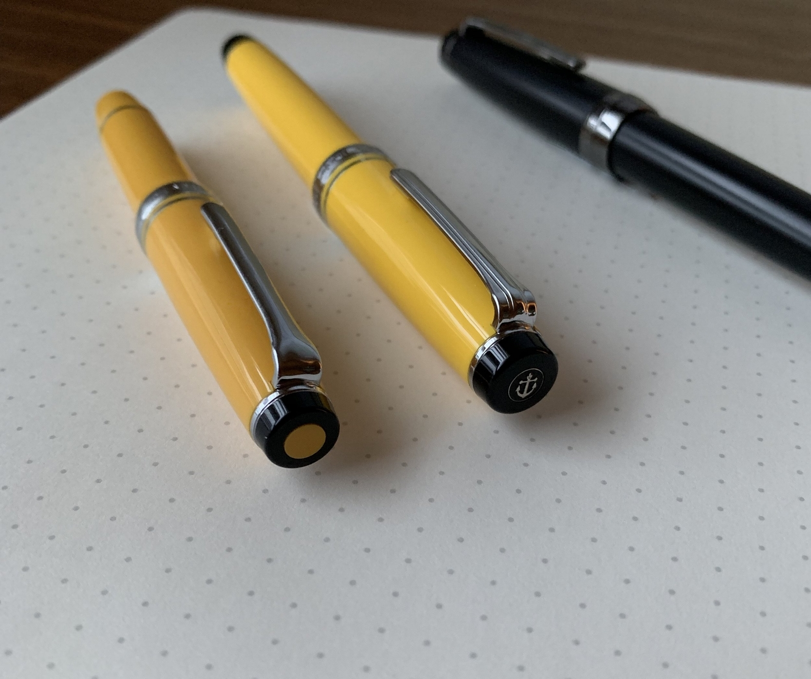 The Nagasawa cap finial (left) compared against the standard Sailor design (right). Note that the yellow used in the Sapporo Mini is a deeper, mustard yellow, which I prefer to the brighter yellow acrylic used on the Pro Gear Color.