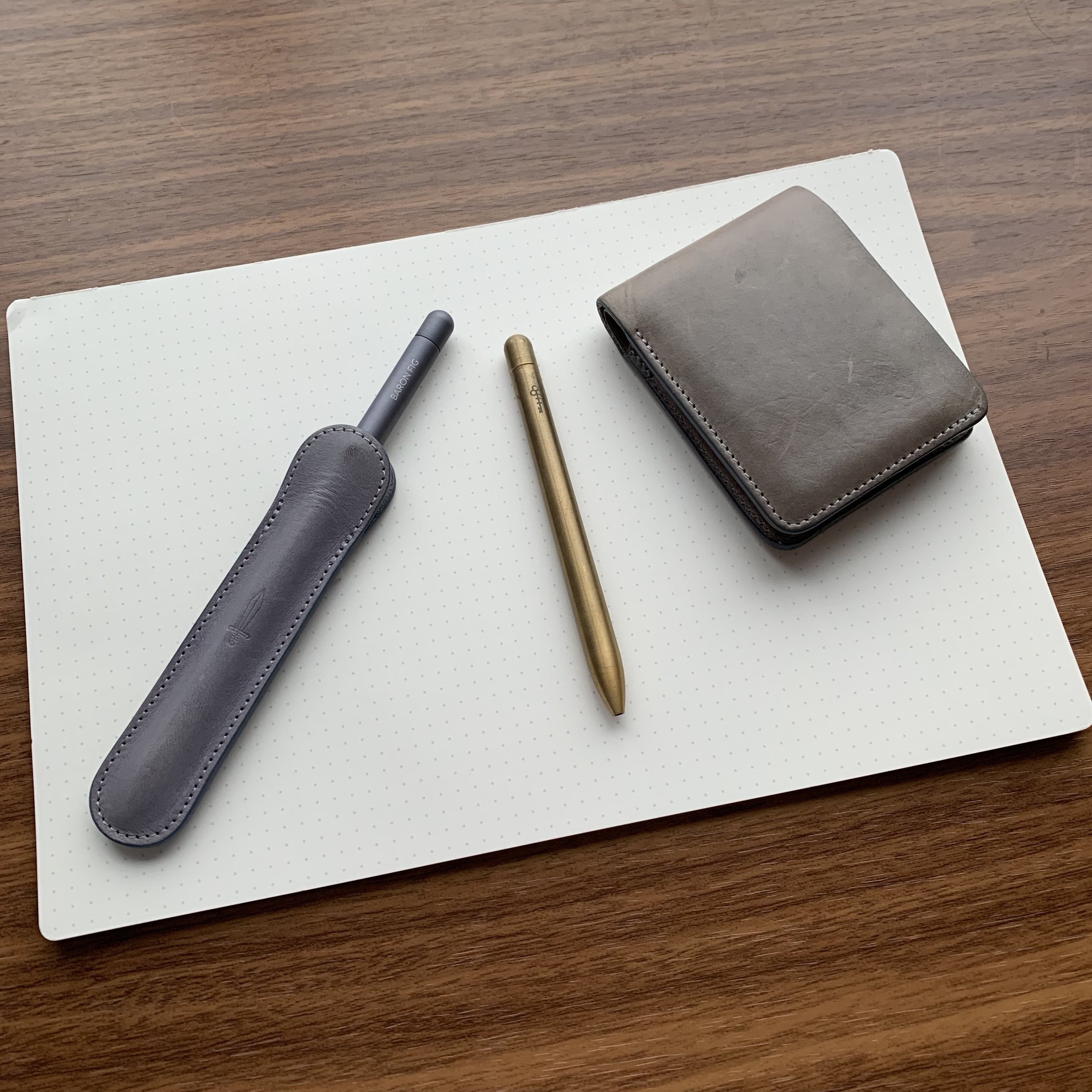 """Pictured from left: Squire Rollerball in """"Sheath"""" Pen single pen sleeve; """"Lock"""" Brass limited edition Squire (check out that patina!) and my getting-worn-in slim bifold wallet. All of these products are sitting on top of a Mastermind desk pad."""