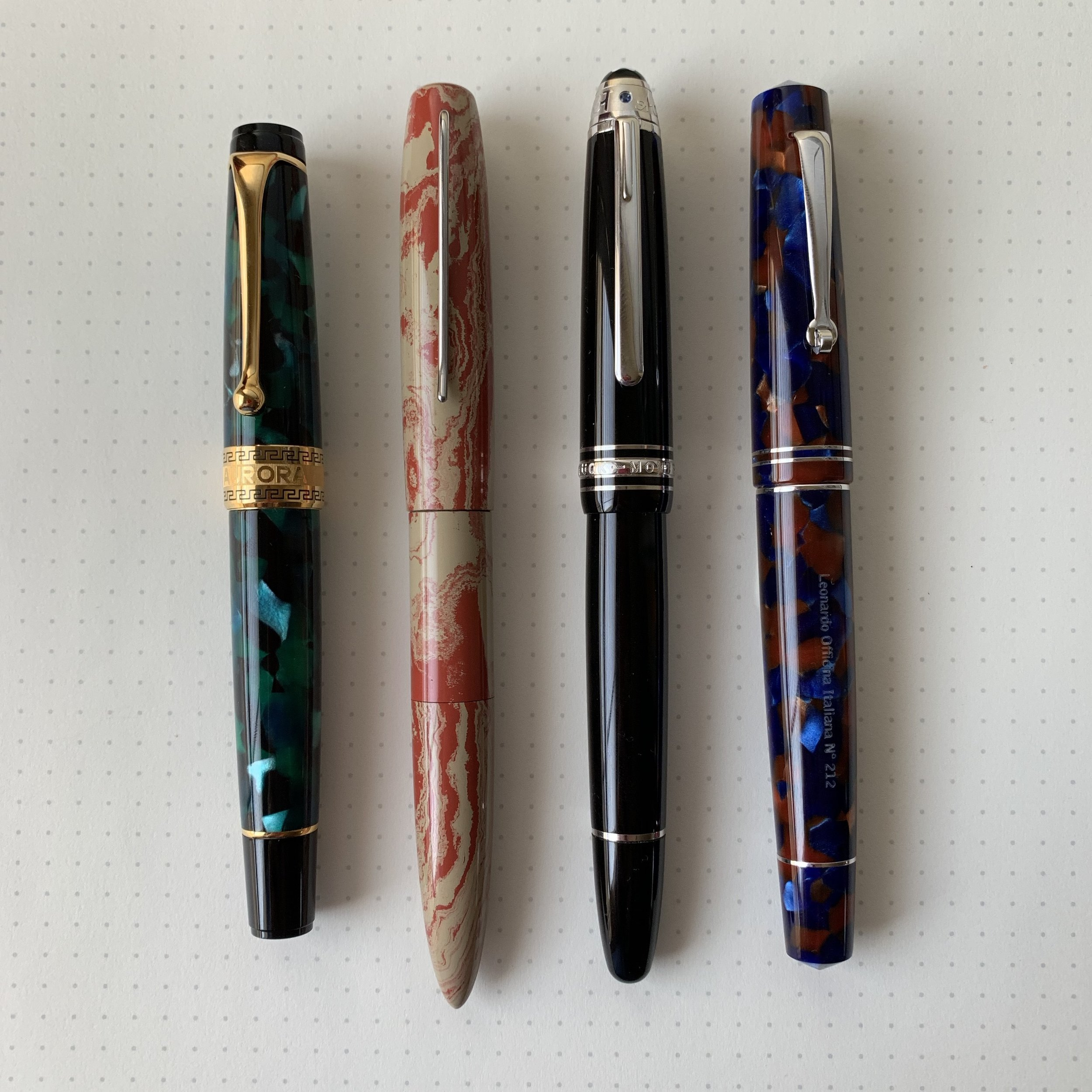 A comparison photo, from left:  Aurora Optima , Desiderata Soubriquet, Montblanc 146, and  Leonardo Momento Zero .