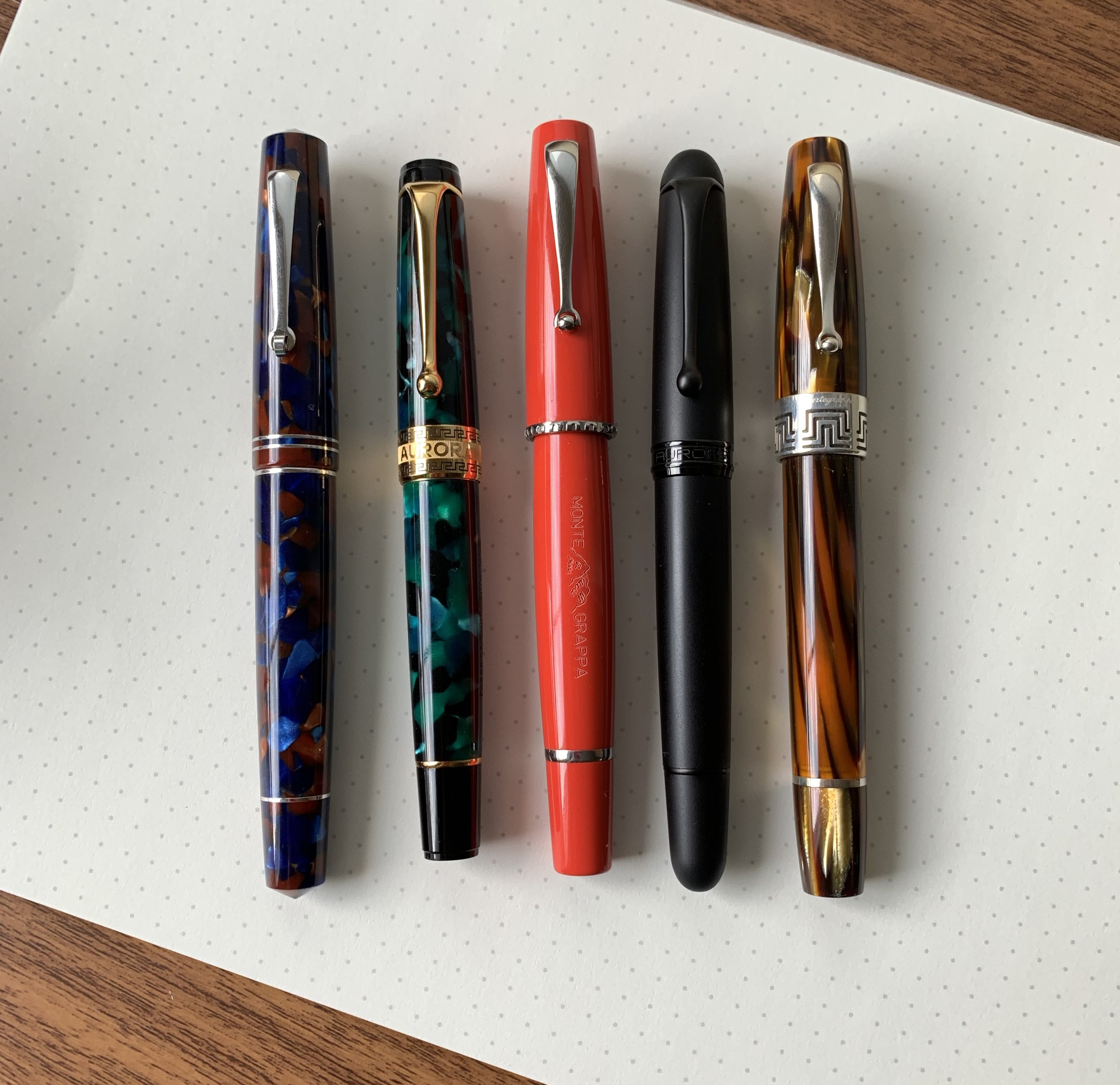 "The Montegrappa Monte-Grappa (center) compared against some other Italian ""flagship"" pens. From left, the  Leonardo Momento Zero in ""Pietra Marina"" Sea Stone , an  Aurora Optima in Emerald , the  Aurora 88 Unica Nera , and a  Montegrappa Extra 1930 in Turtle Brown ."