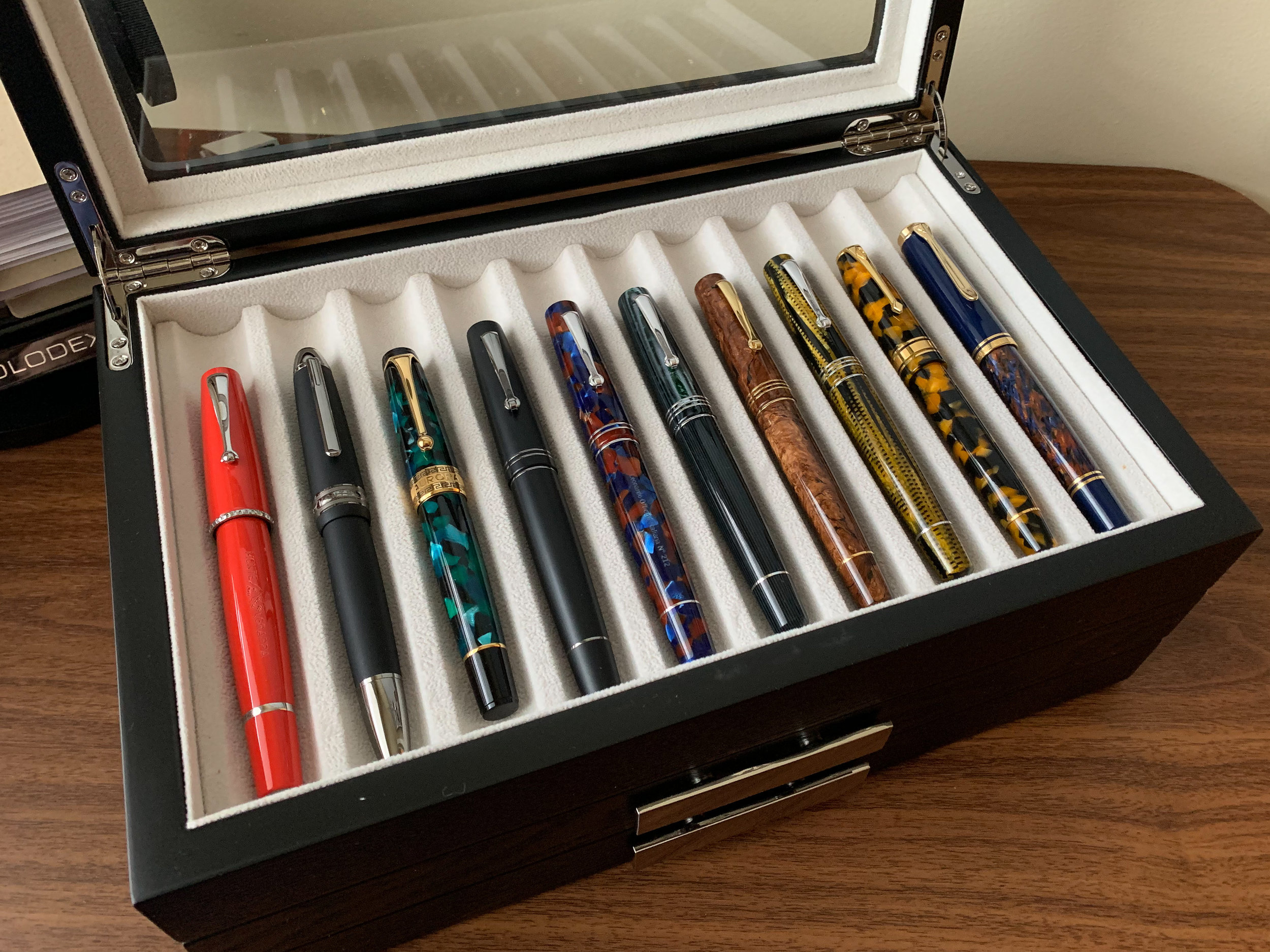 "A Leonardo Momento Zero ""Family Snapshot,"" with some other pens for comparison purposes. From left: Montegrappa Monte-Grappa, Montblanc 146, Aurora Optima, Momento Zeroes in Matte Black, Sea Stone Acrylic, Arco Verde celluloid, Burlwood celluloid, and Burkina celluloid, Conway Stewart Model 100, and a Pelikan M800 Stone Garden."