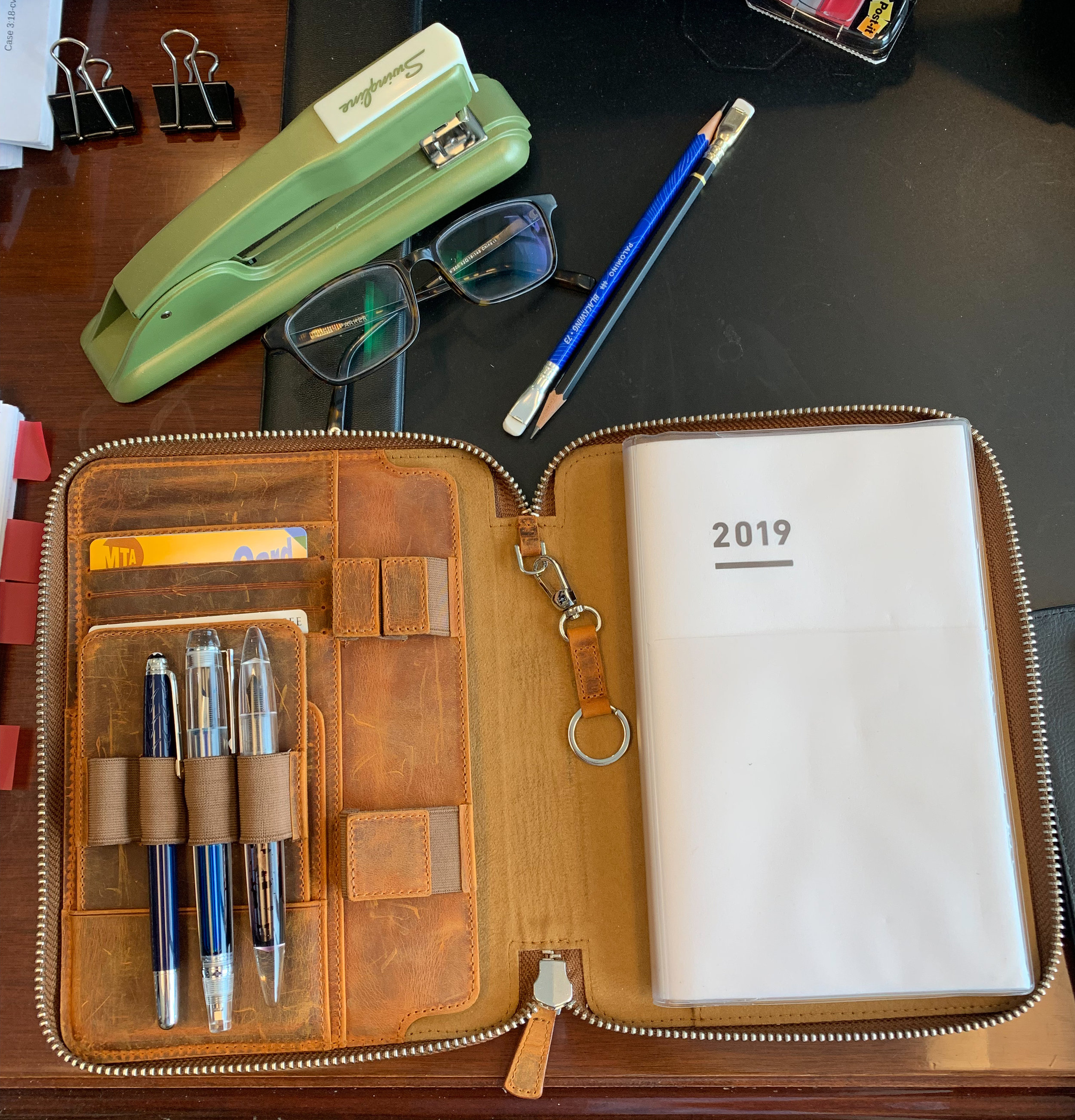 An overview of the A5 Zipfolio on my desk at work, complete with three pens and a Jibun Techo Planner System.