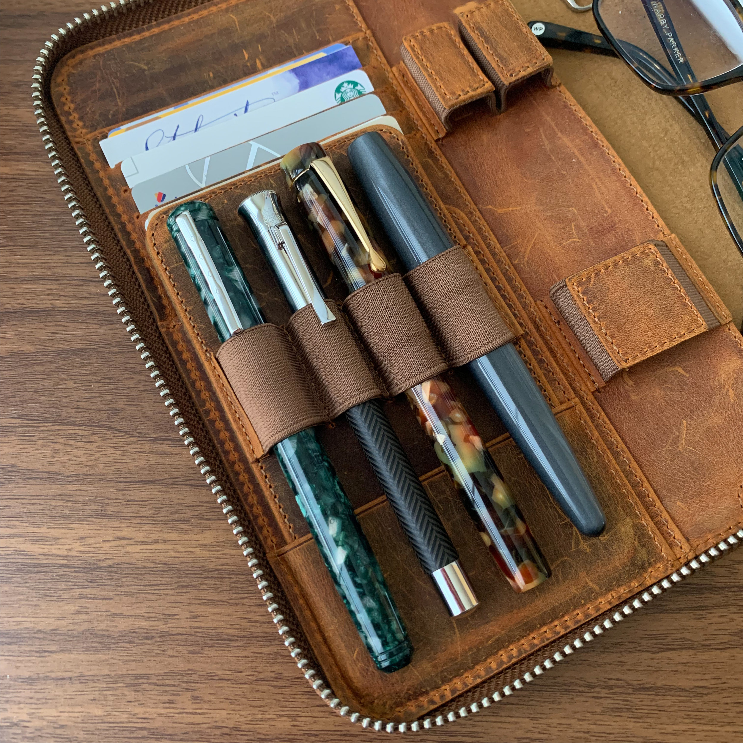 "The two on the left are my 2019 D.C. Pen Purchases, shown here in a  Galen Leather A5 Zippered Notebook Folio in Crazy Horse Brown distressed leather . Check out  my review of the Galen Leather A5 ""zipfolio""  here."