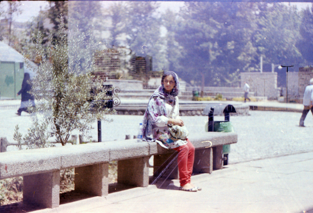 He once told me he had lost the negatives.  One day before I leave, he took some photos of me, in the central part of Tehran, Meydoon Vali-Asr, Enghelab. It was a s strange day, I had so many mixed feelings; excitement, fear, feeling an absence.  He found the negatives. I am holding my breath while looking at them. This is not me. I left me that day on that grey bench. As I am writing, I remember my bus ride on the way back home.  Looking out the window, passing by the sad old  trees of Vali-Asr, looking at their reflection on the window, the uncertainties, the grief.  Those trees are far and gone, this poetic image is only an imagination.  Photo by Ardalan Zandyavari