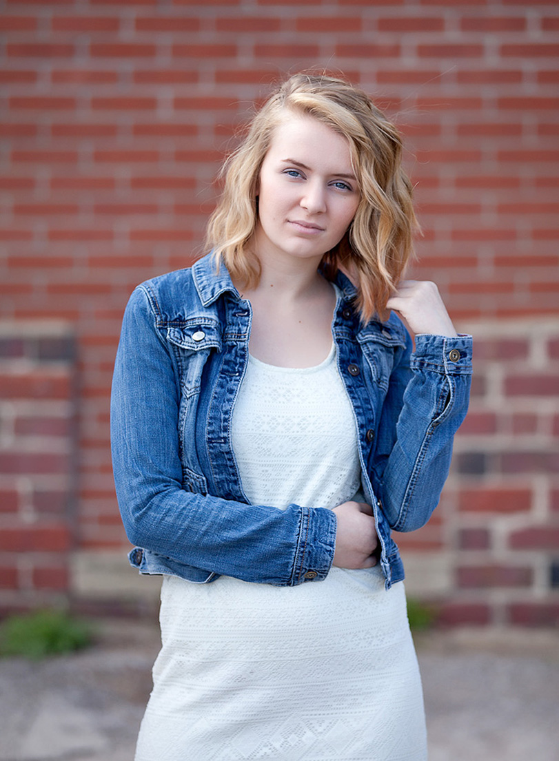 blonde senior girl with white dress and jean jacket in front of brick building in Orrville, Ohio