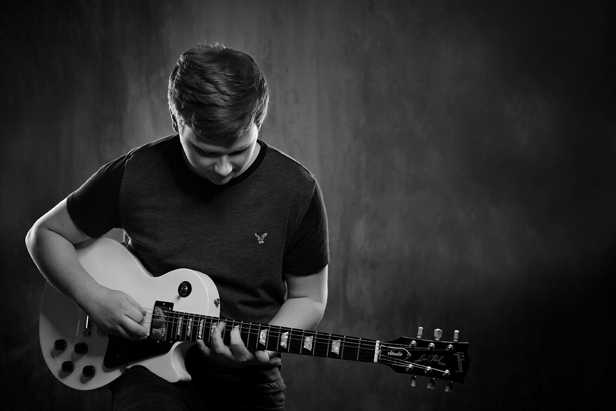 black and white photo of a senior guy playing a Les Paul guitar in-studio grungy background in Fredericksburg, Ohio
