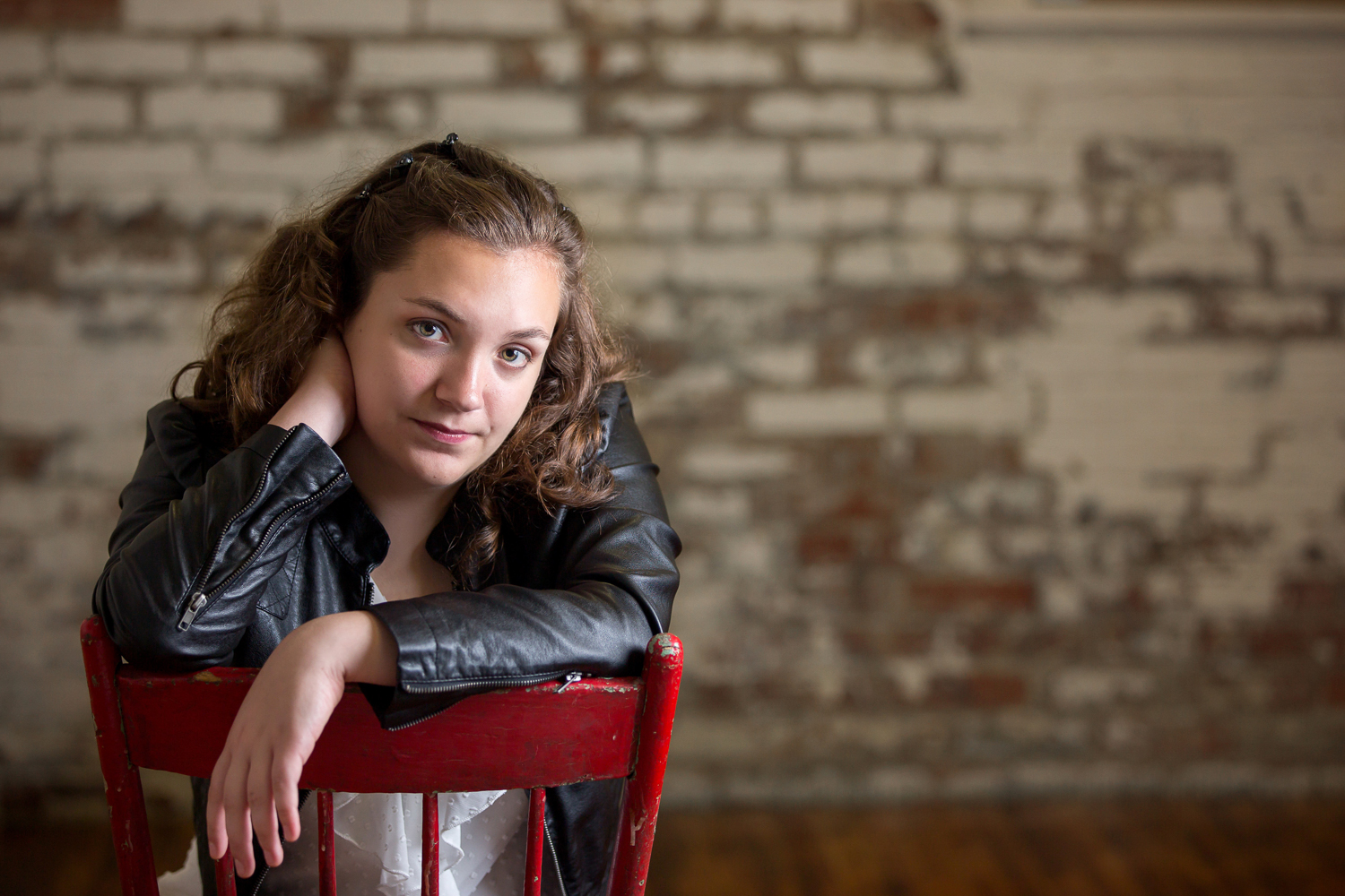 brunette senior girl wearing a white top and leather jacket sitting backward in a red chair with grungy pealing white paint on exposed brick wall behind her in Wooster Ohio