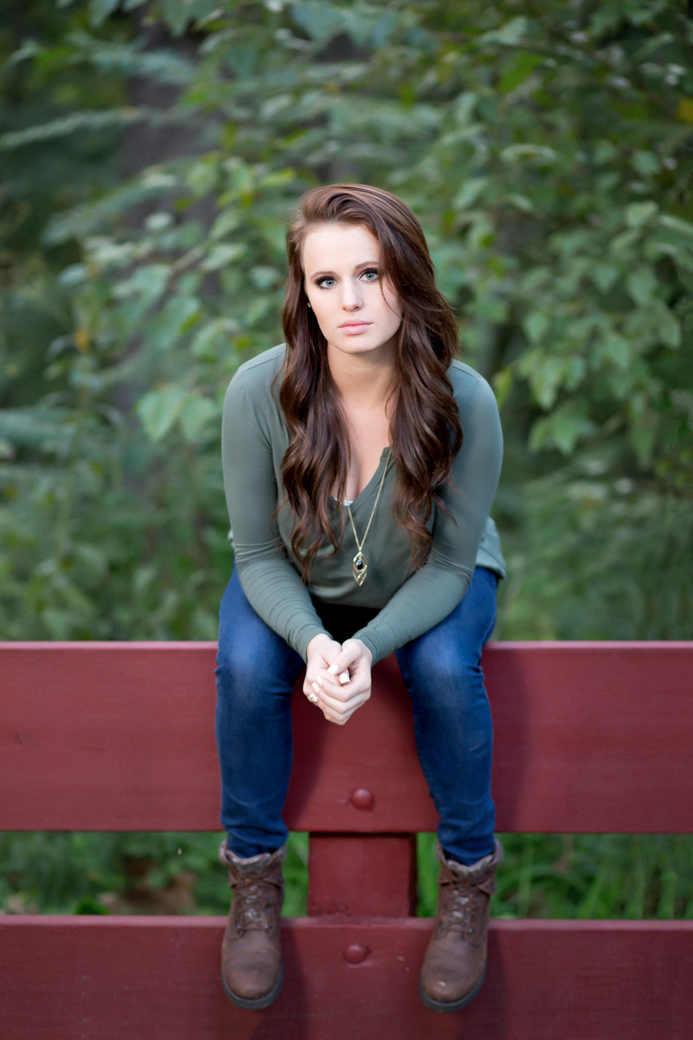 brunette senior girl wearing green long-sleeve top blue jeans and boots sitting on a red wooden rail with greenery behind her in Fredericksburg Ohio