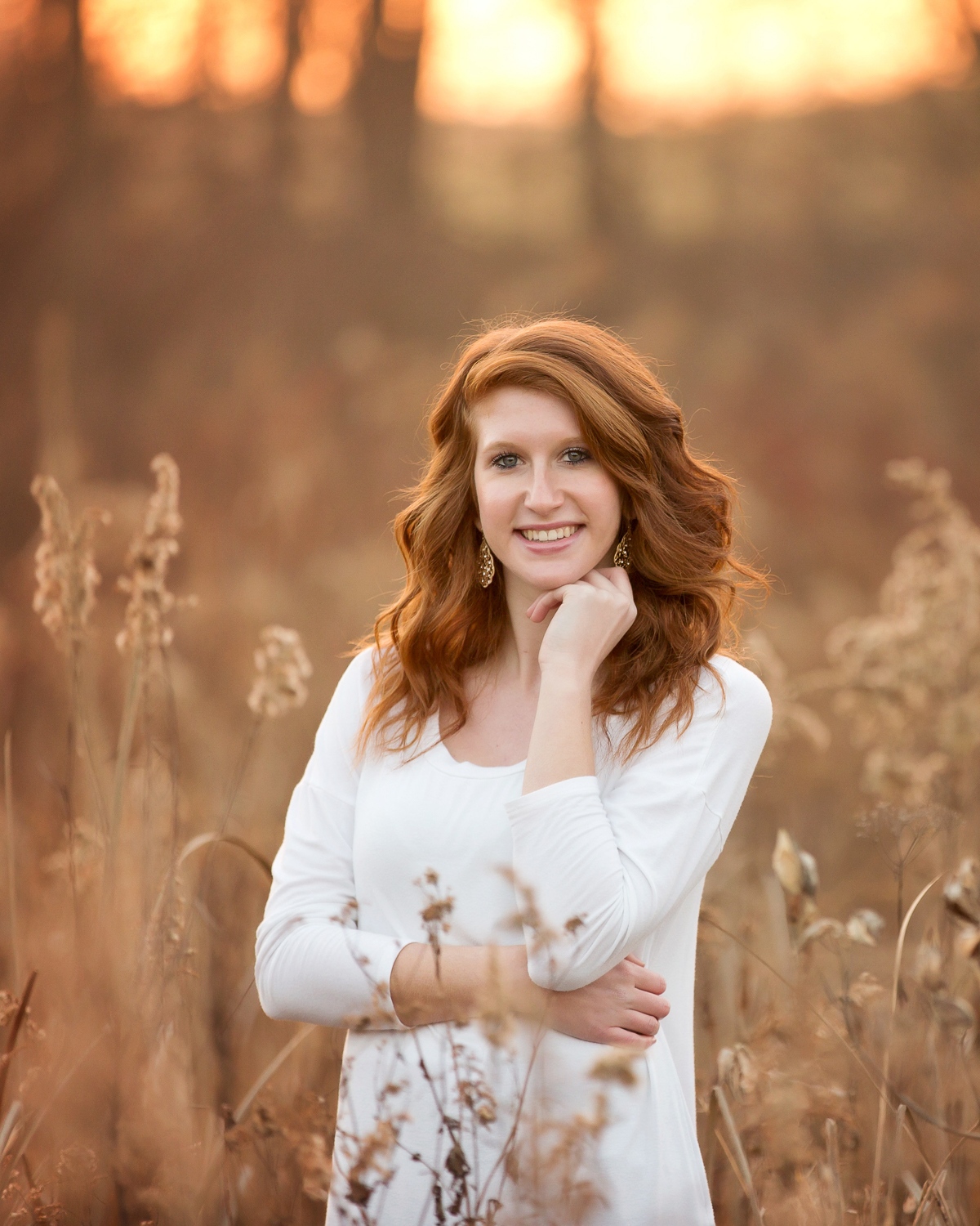 red-headed senior girl wearing a white dress at sunset staning in a field of dried weeds with a woods and sunset behind her in Fredericksburg Ohio