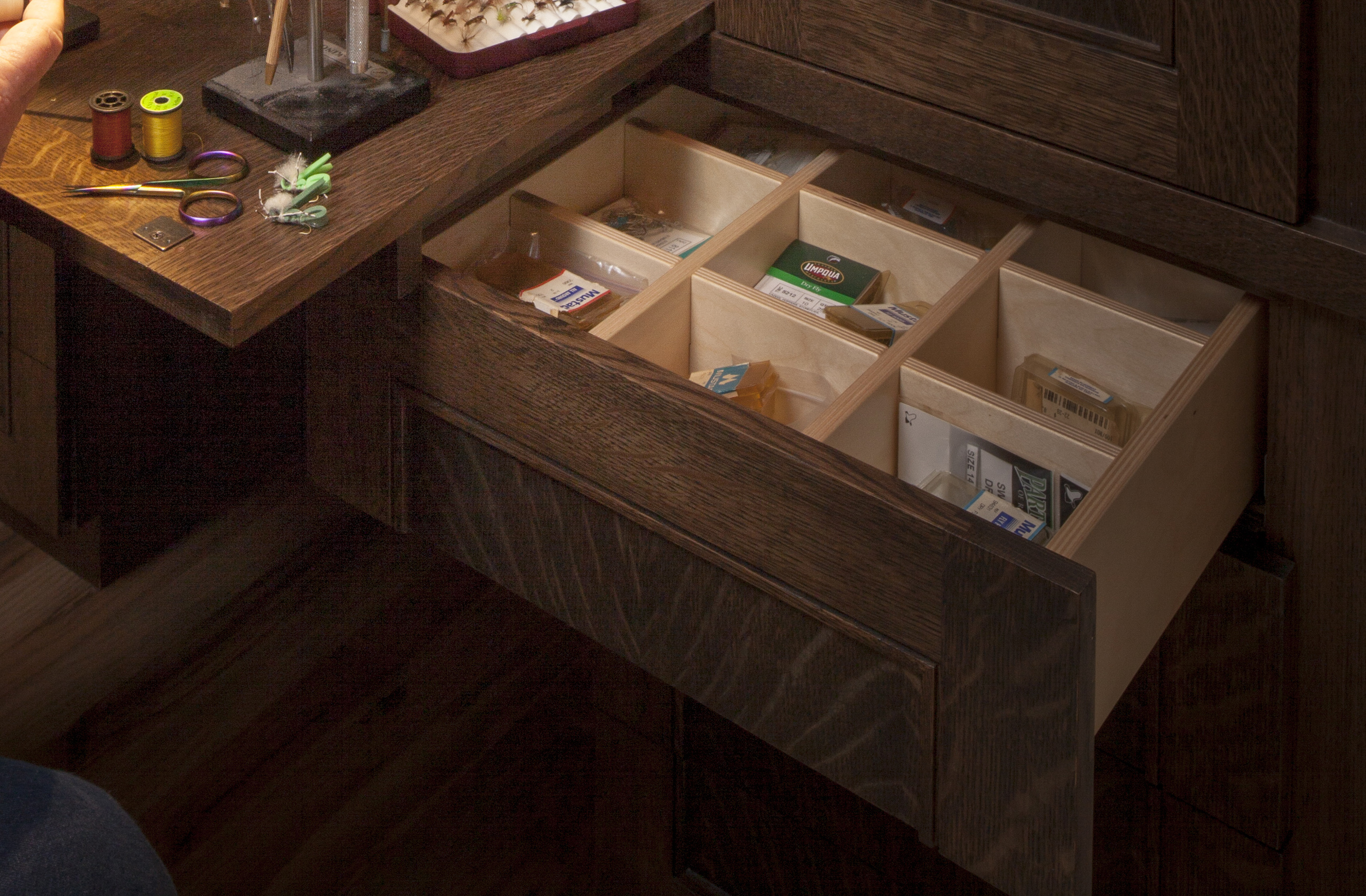 Compartments hold the multiple and necessary components for tying a proper fly. Built-in soft close drawers, which are included throughout the home, are part of this construction as well.  (Materials: Quarter-sawn white oak with stain and lacquer finish. Interior compartments are soft maple with clear lacquered finish - Click image for larger view.)