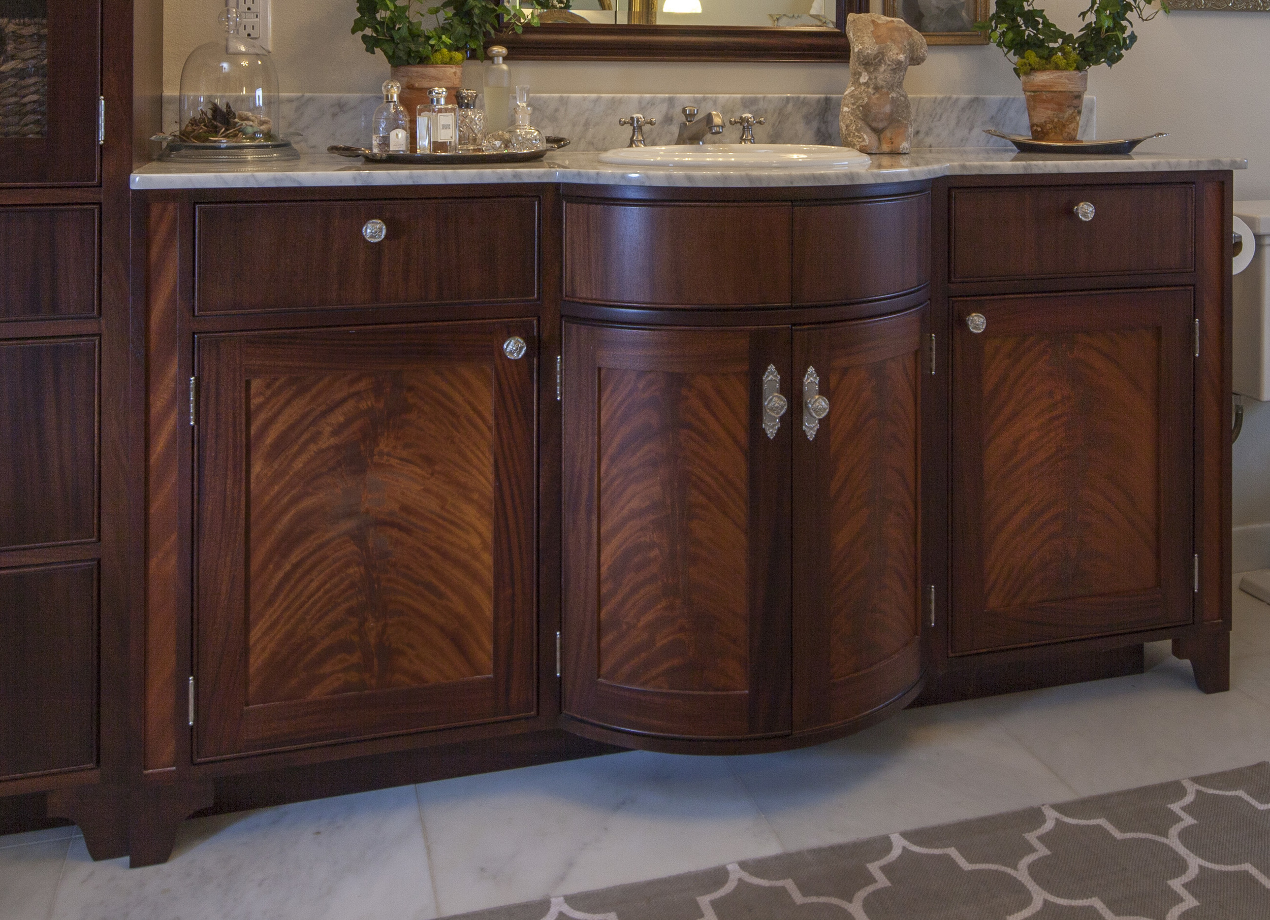 Bathroom vanity by Reznikoff Custom Furniture. Built from crotch mahogany, the curved door treatment makes a notable statement in fine furniture.