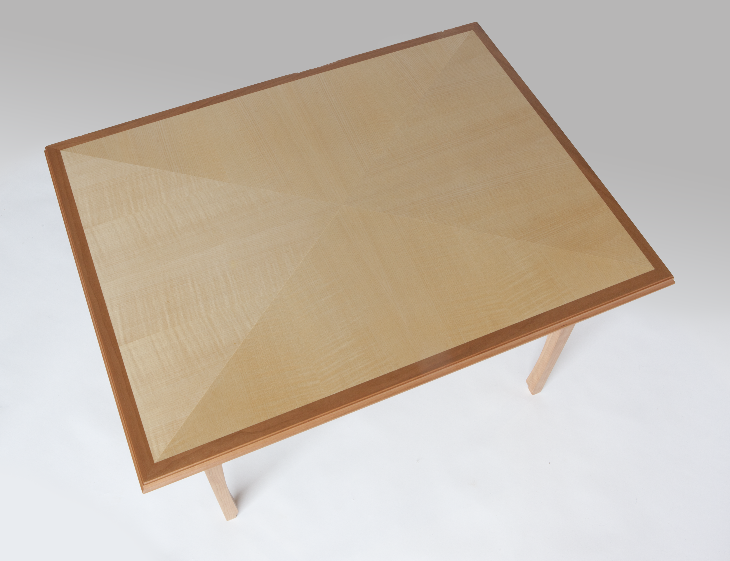 """Coffee table of quarter figured sycamore, laid-up in the """"reverse diamond"""" pattern with cherrywood edge, trim and base. Of note is how the reverse diamond pattern changes contrast with its angle to the light.  Dimensions: 33"""" x 25"""" x 20"""" high  Design by Reznikoff Custom Furniture"""
