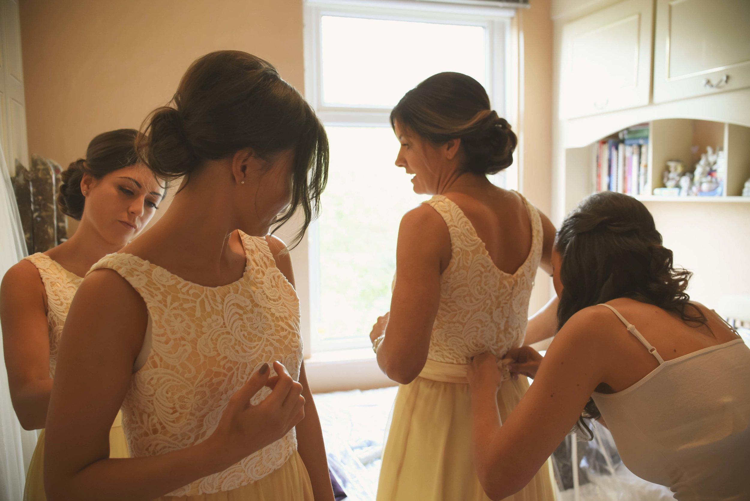 Bridesmaids putting dresses on