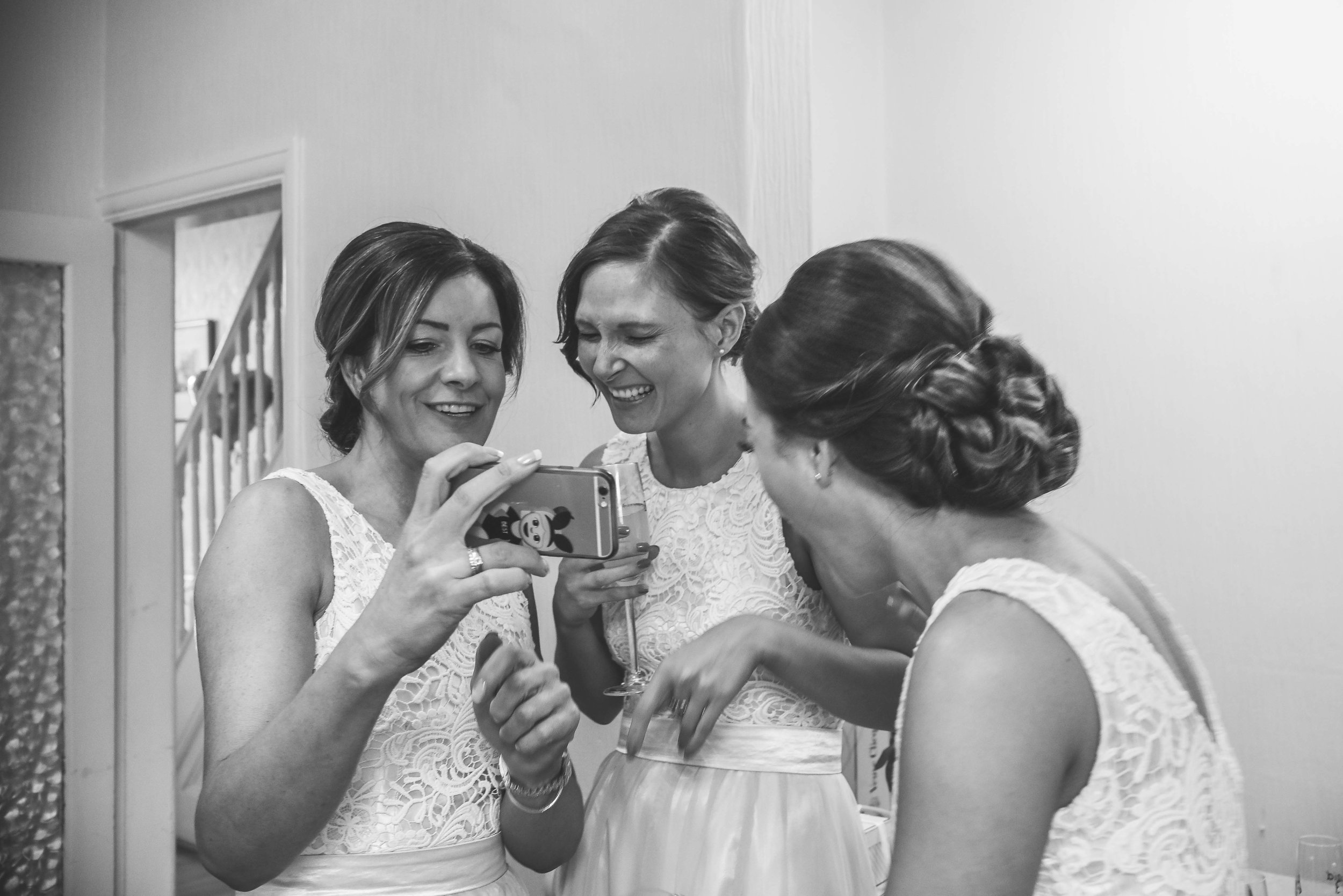 Bridesmaids laughing at  a picture black and white