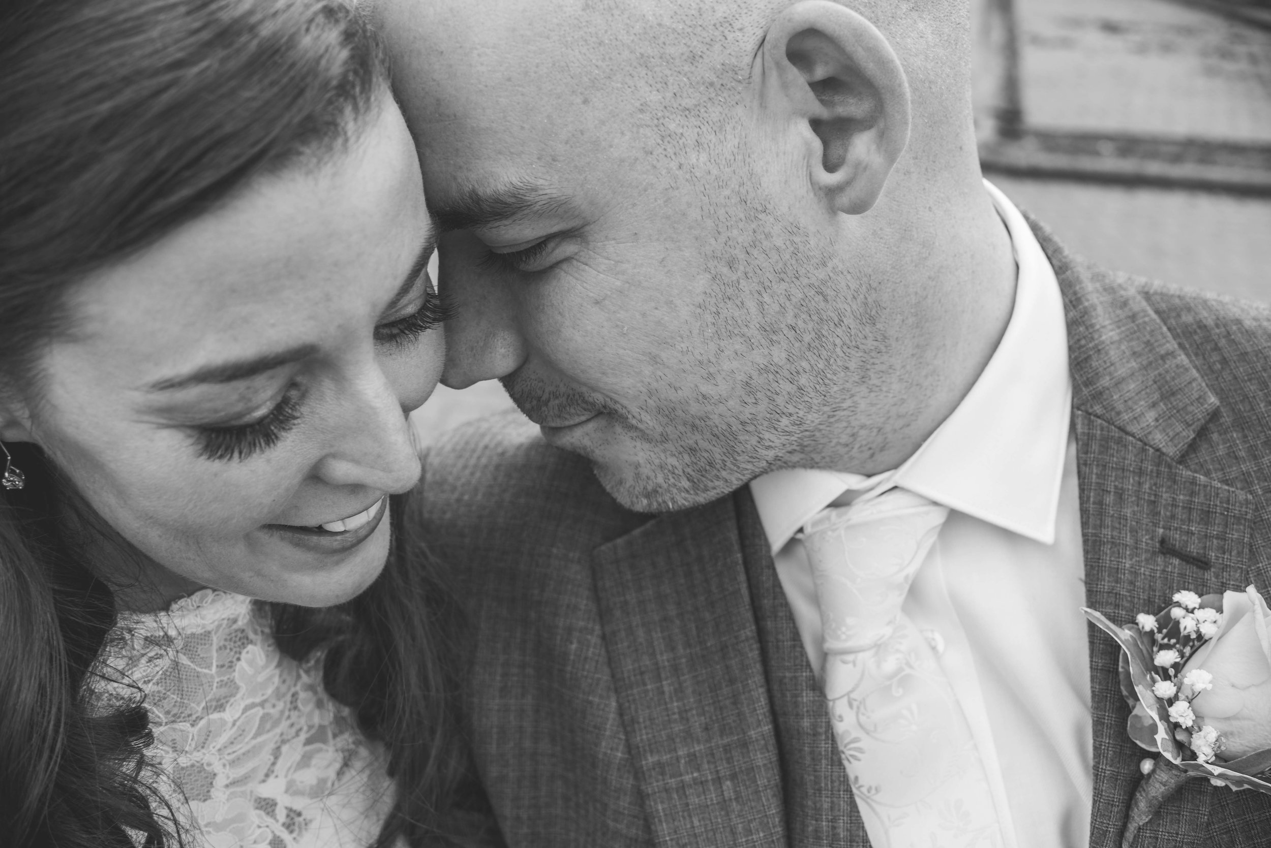Bride and groom faces touching black and white
