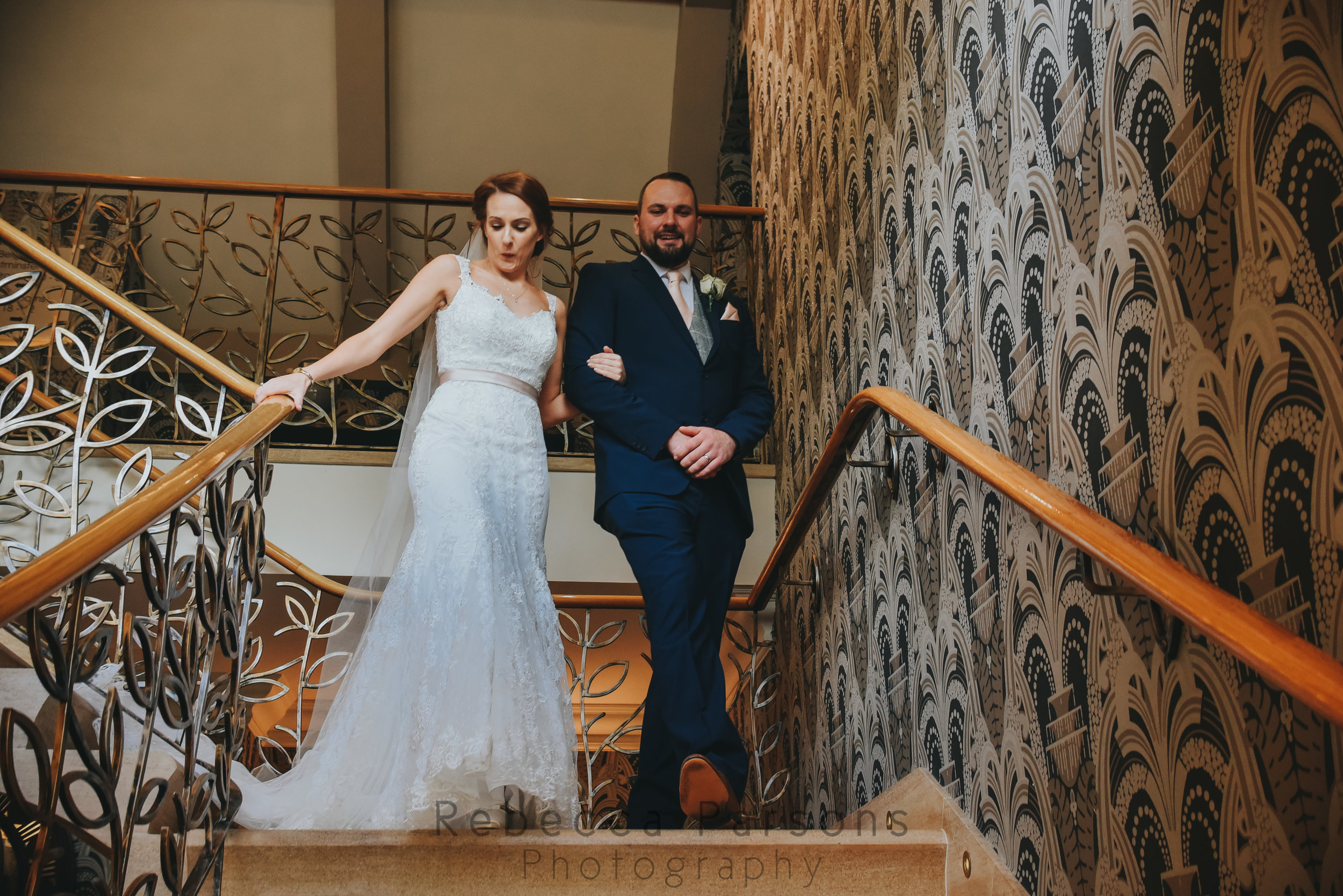 Bride and her brother walking down the stairs