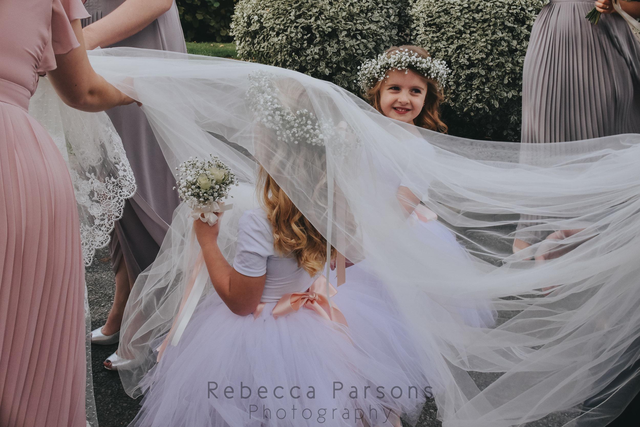 Flower girls hiding under the bride's veil