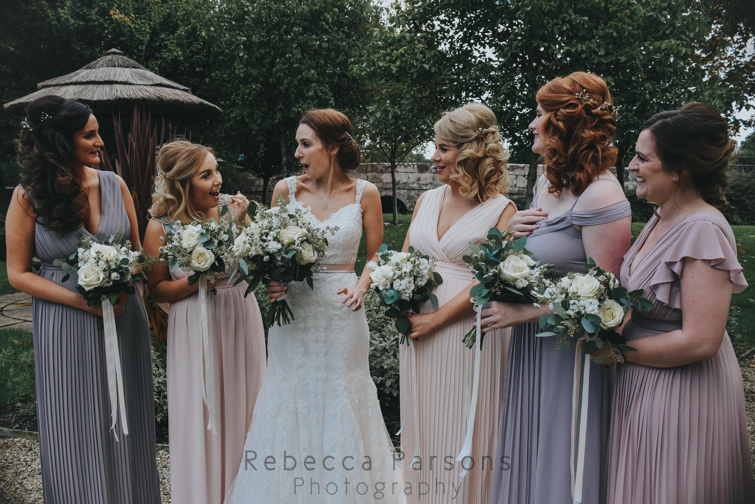 Bride in landscaped gardens with bridesmaids