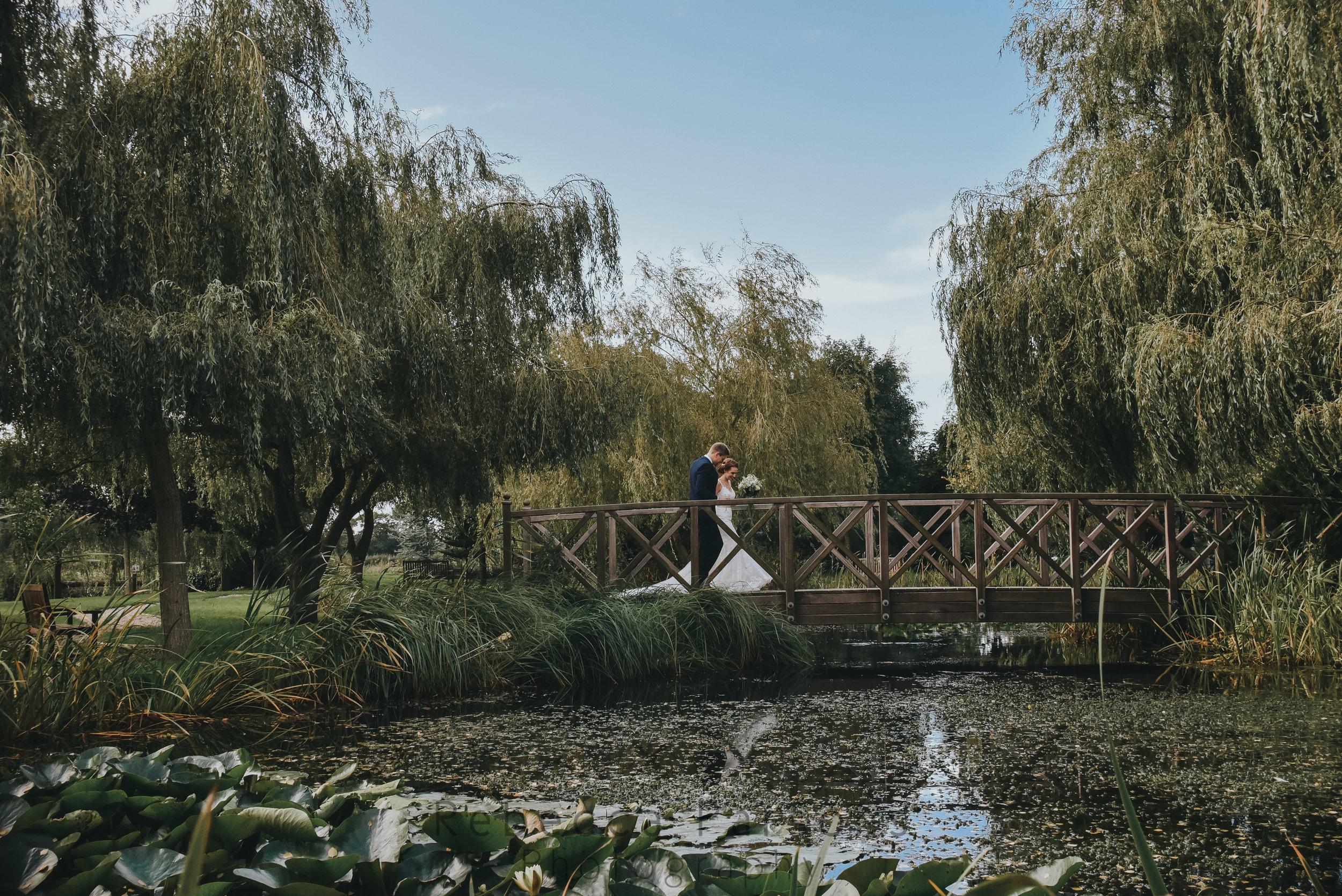 Bride and groom on bridge in sensory garden