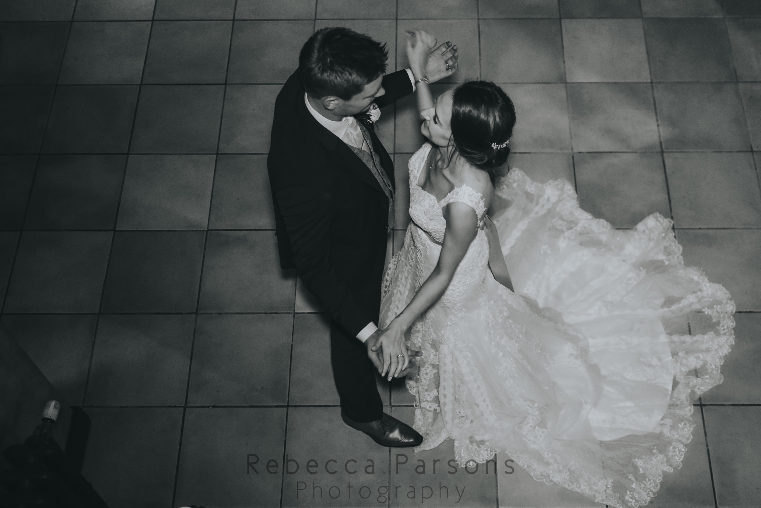 The bride and groom holding hands in black and white
