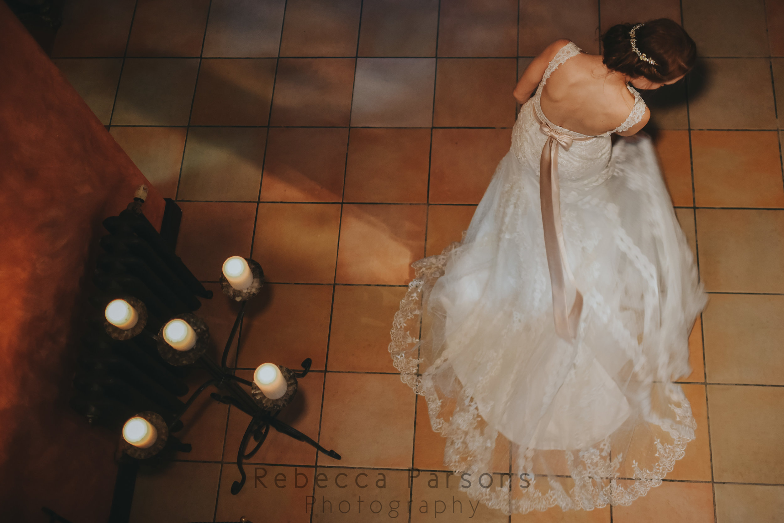 The bride standing by candles and adjusting her dress