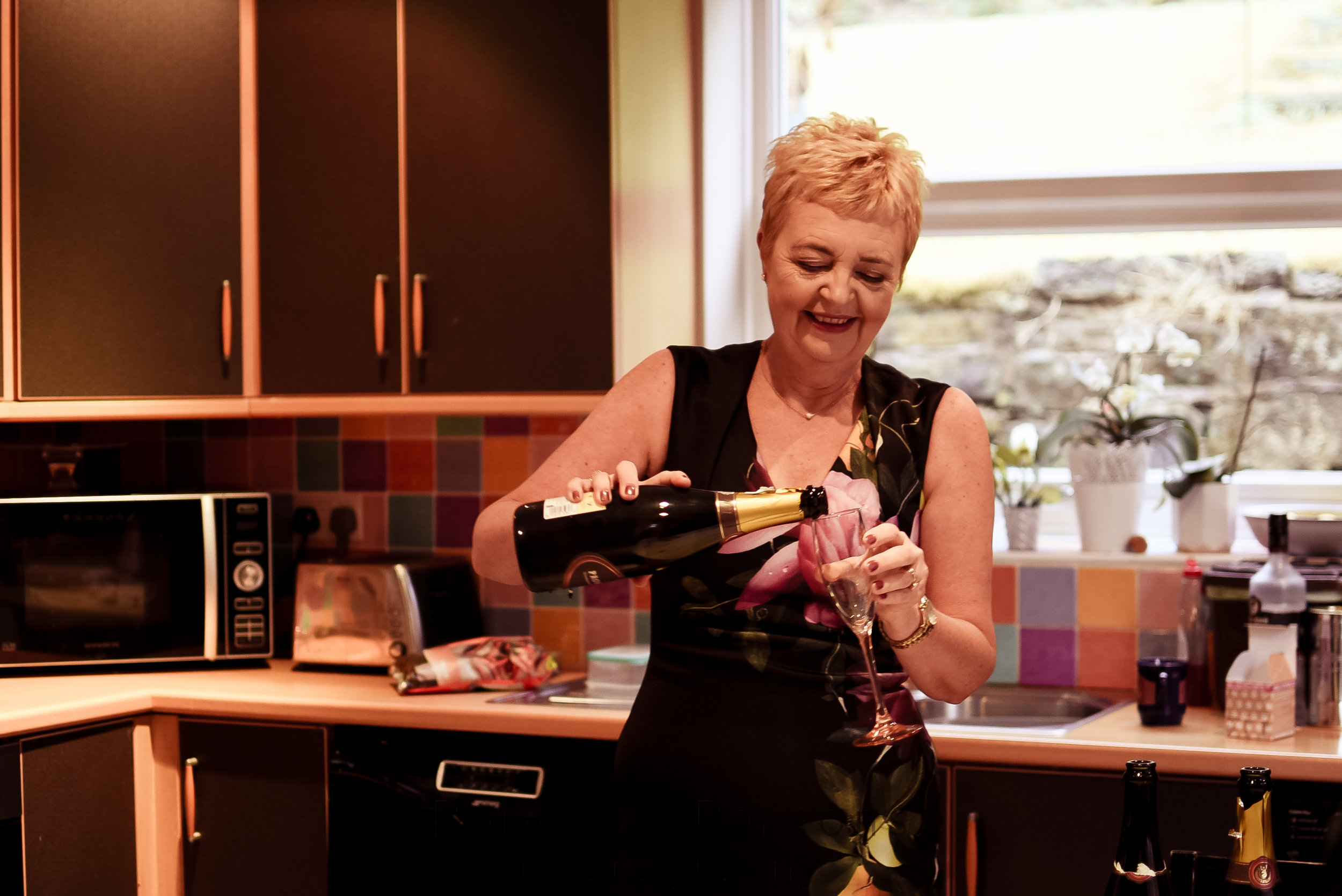 Mother of the bride pouring prosecco